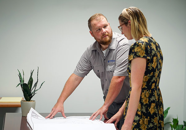 Man showing blueprints to woman