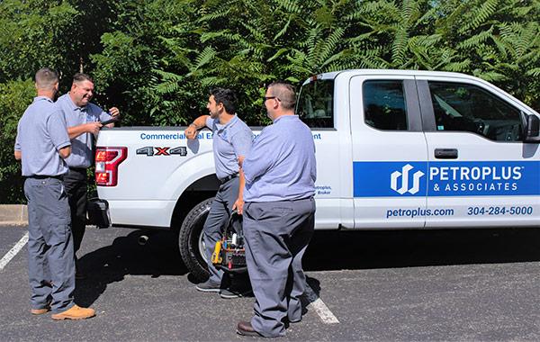 Maintenance crew standing around pickup truck